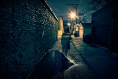 Shadow of a scary man in a dark urban city alley at night. Stock Photo