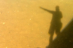 Shadow Silhouette of a Man. Standing over Water Pointing Royalty Free Stock Photography