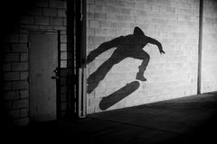 Shadow skateboarder. The shadow of a skateboarder doing a trick on the wall of an industrial building Royalty Free Stock Image