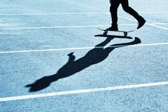 Shadow of a skateboarder on asphalt. Blue toning. Dark shadow of a skateboarder on asphalt. Blue toning royalty free stock photo