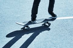 Shadow of a skateboarder on asphalt. Blue toning. Shadow of a skateboarder on asphalt. Active recreation. Blue toning royalty free stock images
