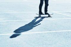 Shadow of a skateboarder on asphalt. Blue toning. Shadow of a skateboarder on asphalt. Active recreation. Blue toning royalty free stock image