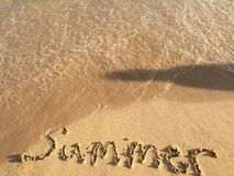 Shadow of someone watching the word summer being washed away. Royalty Free Stock Photography