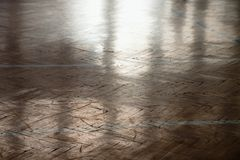 Shadow of sportsman. Window curtain wall reflecting in worn parquet floor at school gym. Royalty Free Stock Photography