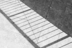 Shadow of the steel handrail on the concrete floor.  stock image