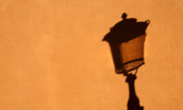 Shadow of street lamp on yellow wall. Black shadow of old street lamp on yellow wall closeup pattern Royalty Free Stock Image