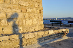 Shadow of street telescope on embankment of the sea Royalty Free Stock Images