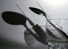 Shadow of syringe. Glass with syringe and spoon and its shadow on the white background Royalty Free Stock Image