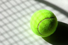 Shadow Tennis. Shadow of tennis racket and strings on a ball royalty free stock image