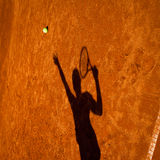 Shadow of a tennis player in action Stock Photos
