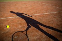 Shadow of a tennis player in action on a tennis court. Conceptual image with a tennis ball lying on the court and the shadow of the player positioned in a way Royalty Free Stock Image