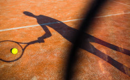 Shadow of a tennis player in action on a tennis court Stock Photo