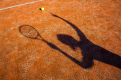 Shadow of a tennis player in action on a tennis court. (conceptual image with a tennis ball lying on the court and the shadow of the player positioned in a way Royalty Free Stock Photography