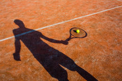 Shadow of a tennis player in action on a tennis court. (conceptual image with a tennis ball lying on the court and the shadow of the player positioned in a way Royalty Free Stock Photos