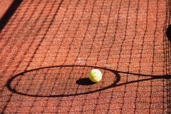 Shadow of a tennis racket and ball on court Stock Photography