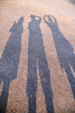 Shadow three of people action posting on ground background Royalty Free Stock Photo