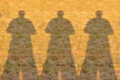 Shadow of Three Photographer Man on Field Royalty Free Stock Images