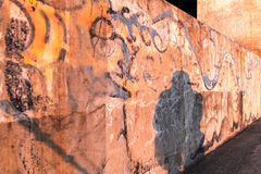 Shadow of Time. The viewer steps into the shadow in this picture and experiences the aging graffiti on the concrete wall while illuminated by a golden, setting Stock Image