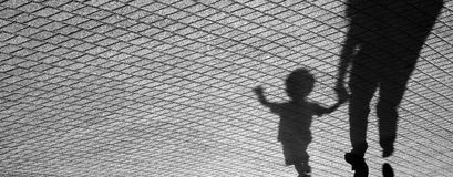 Shadow of a toddler and a man. Blurry shadow of a joyful toddler boy walking hand in hand with his father royalty free stock image