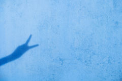 Shadow of two fingers up on blue wall background royalty free stock photography