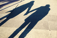 Shadow of two people holding hands on a walk Royalty Free Stock Photo