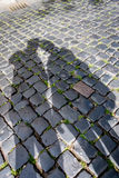 Shadow of two people over brick floor. In the street Stock Image