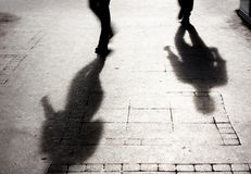 Shadow of two person on patterened sidewalk Stock Photos
