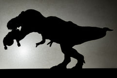 Shadow of tyrannosaurus biting a body  on wall. No logo or trademark Stock Image