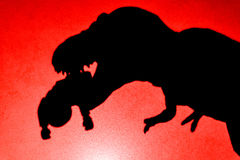 Shadow of tyrannosaurus biting a body  on wall in red close up Royalty Free Stock Image
