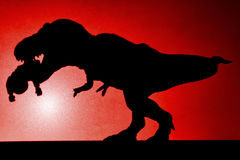 Shadow of tyrannosaurus biting a body  on wall in red. No logo or trademark Royalty Free Stock Image
