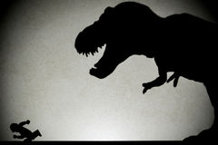 Shadow of tyrannosaurus chasing human  on wall Stock Photography