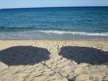 Shadow of umbrellas on the sand by the sea Stock Photography