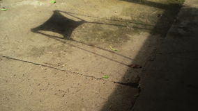 Shadow of unrecognizable boy child jumping from swing seat in summer afternoon.