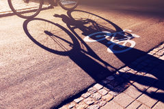 Shadow of unrecognizable cyclist on bicycle lane Stock Photos
