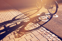 Shadow of unrecognizable cyclist on bicycle lane Royalty Free Stock Photos
