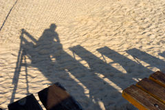 The shadow of the viewer on a bench on the beach at the net Stock Photos