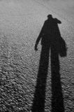 Shadow. A walking mans shadow on the asphalt road Royalty Free Stock Photography