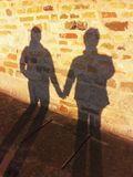 Shadow on the wall. Old wall with shadow of a couple holding their hands royalty free stock image
