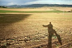 Shadow of a waving man in sunny autumn scenery Royalty Free Stock Image
