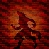 Shadow of werewolf on a brick wall Stock Image