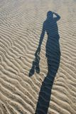 Shadow on Wet Sand. A shadow of a person holding sandals on the shores of a low tide at sunset Stock Image
