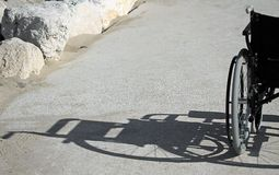 Shadow of a wheelchair on the rocks Stock Photography