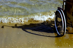 Shadow of a wheelchair in the sand on the seashore Royalty Free Stock Photography