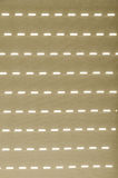 Shadow of the window shutter on the neutral curtain. An interesting pattern created by the light passing through the partially open window shades onto the Royalty Free Stock Images