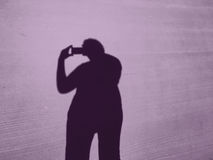 Shadow of a woman with an iPhone makes photos Stock Images