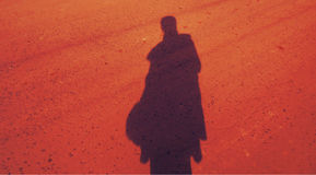 Shadow of a woman. A shadow of a woman on an orange/red background Royalty Free Stock Photos