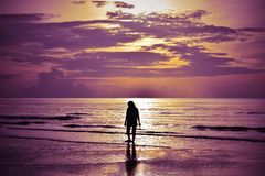 The shadow of a woman walking on the beach at sunrise. Highlight purple and orange. Soft focus. Selective focus stock image