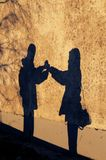 Shadow of young couple facing each other and holding hands. Shadow of happy young couple facing each other and holding hands cast on the side of an old building royalty free stock photo