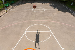 Shadow of Young Man Making Shot on Basketball Net Royalty Free Stock Photos