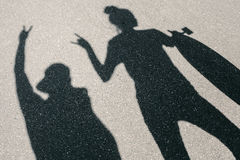Shadow of young man and woman posing with skateboard Royalty Free Stock Image